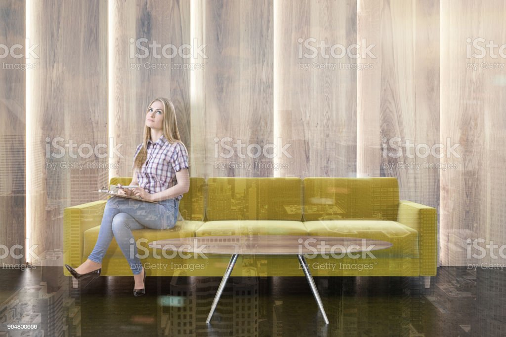 Yellow sofa in a wooden living room, woman royalty-free stock photo