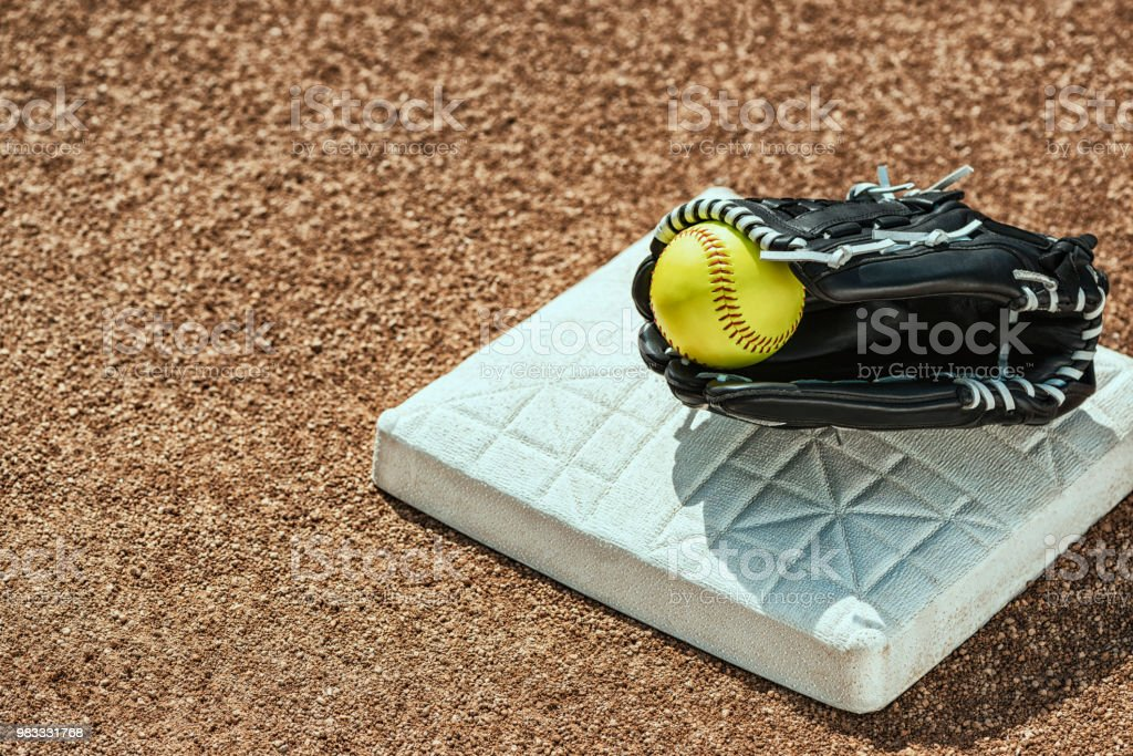 Looking down a new yellow softball inside a black leather glove that...