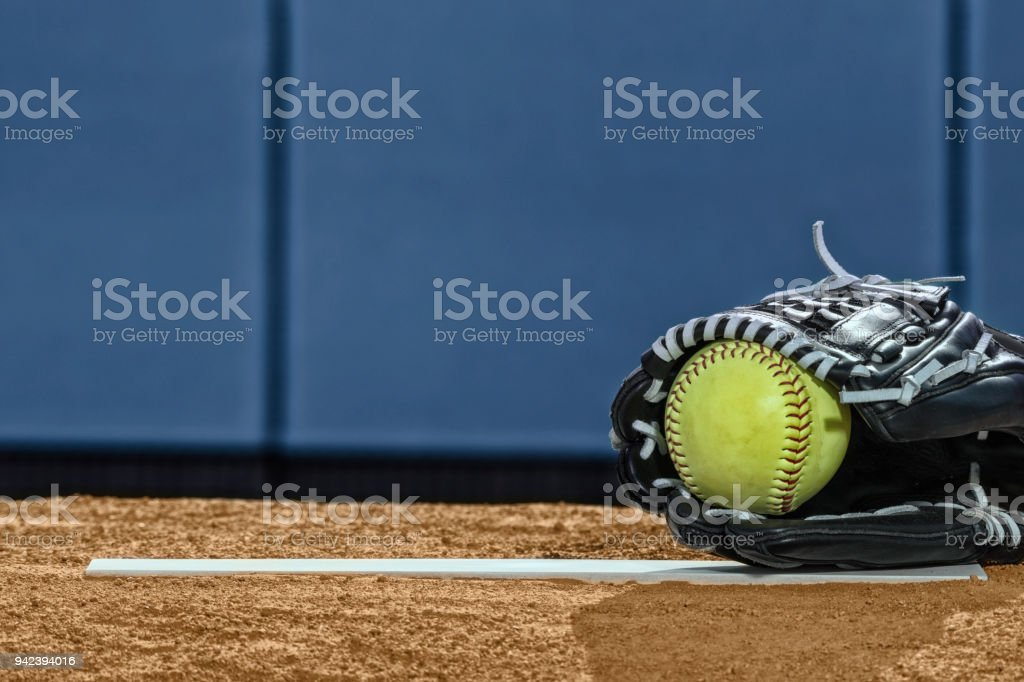A low angle view of a new yellow softball in a black leather glove...
