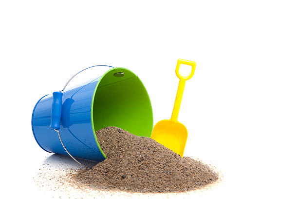 Yellow spade, and blue bucket with sand spilling out stock photo