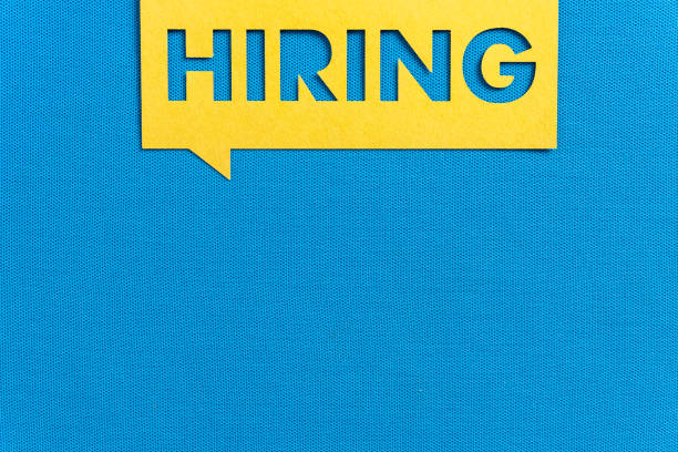 """""""HIRING"""". Yellow speech bubble banner on blank blue textured background. Job vacant and employment concept with copy space. """"HIRING"""". Yellow speech bubble banner on blank blue textured background. Job vacant and employment concept with copy space. help wanted sign stock pictures, royalty-free photos & images"""