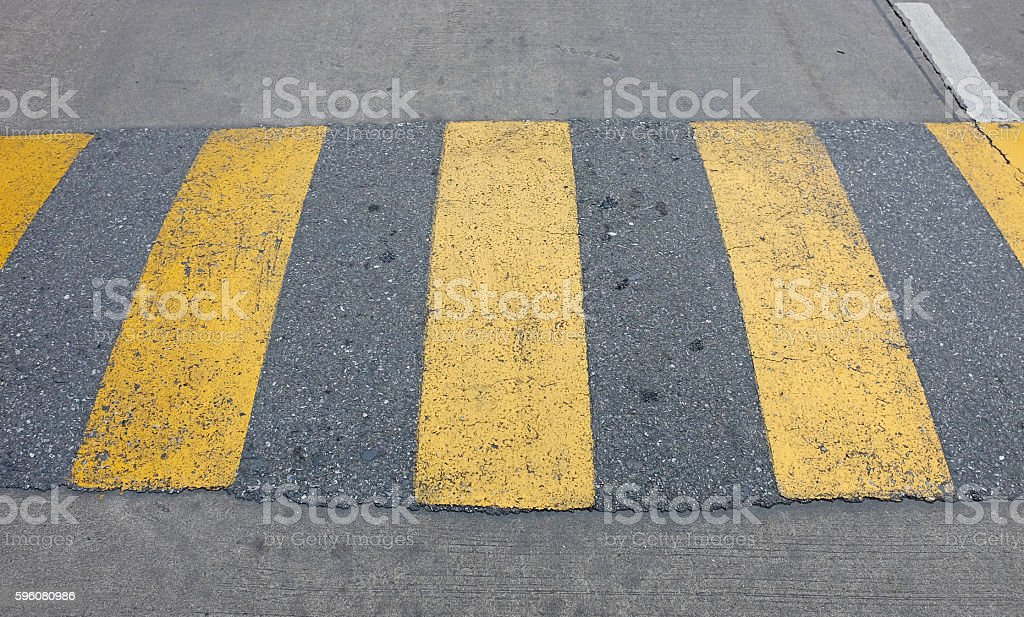 yellow speed bump for slowing traffic stock photo