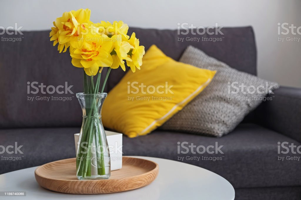 Beautiful yellow spring flowers in a vase standing in the living room...