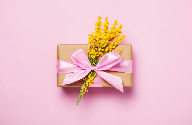 yellow spring flowers on pink background and gift present box. - immagini mimosa 8 marzo foto e immagini stock