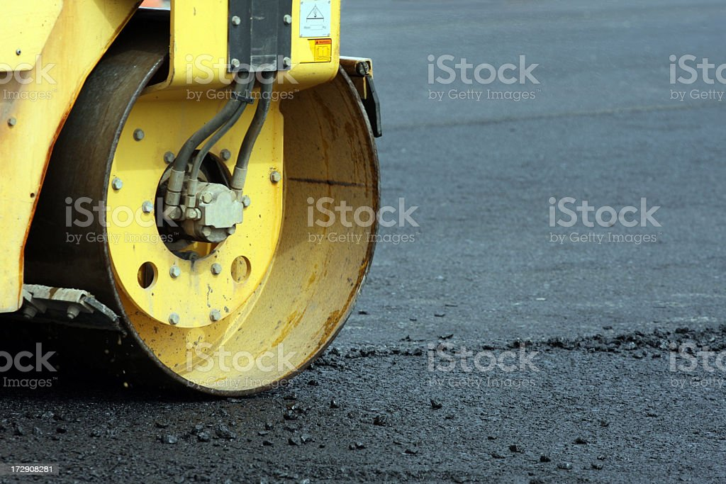Yellow steamroller working on the street royalty-free stock photo
