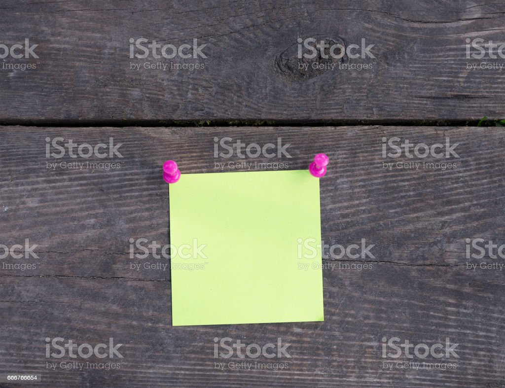 Yellow sticker and pins on wooden wall foto stock royalty-free