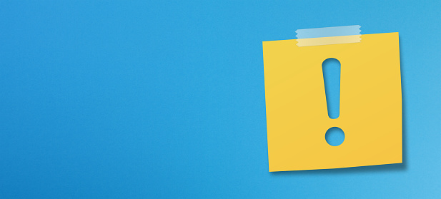 Yellow sticky note paper with exclamation mark on blue background