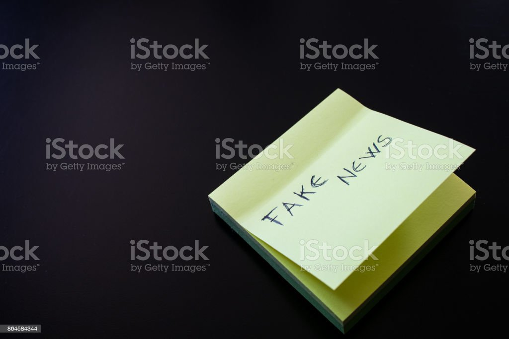 Yellow sticky note with Fake News written on first paper stock photo