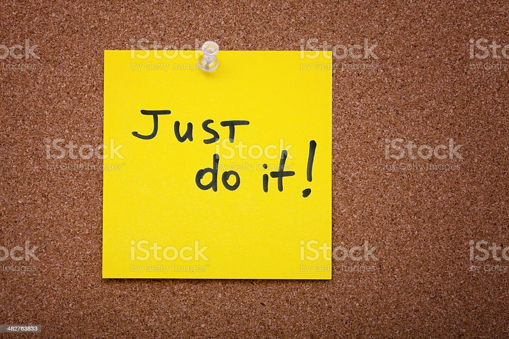 Yellow sticky note with Just do it on cork board royalty-free stock photo