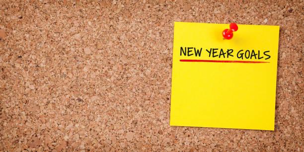 Gelbe Haftnote mit Neujahrszielen und rotem Push Pin auf Kork Board – Foto