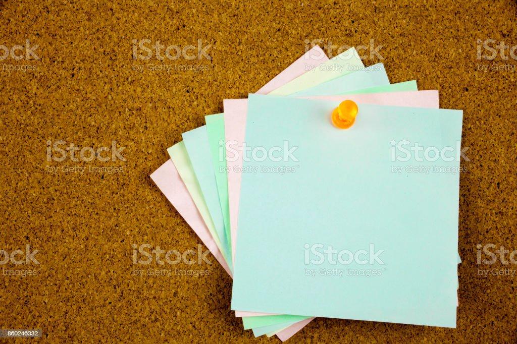 A yellow sticky note writing, caption, inscription colorful sticky notes on cork bulletin board stock photo