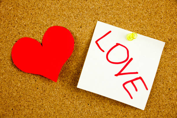 eine gelbe klebrige anmerkung schreiben, beschriftung, inschrift herz mit der liebe. konzept für die liebe. liebe - beste medizin für herzprobleme. in schwarz ext auf einem zettel angeheftet, eine kork-pinnwand - arzt zitate stock-fotos und bilder