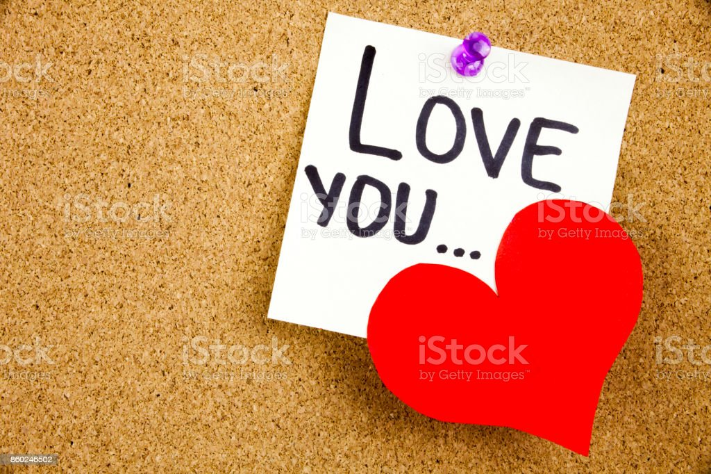 A yellow sticky note writing, caption, inscription Phrase LOVE YOU ... in black ext on a WHITE sticky note pinned to a cork notice board stock photo