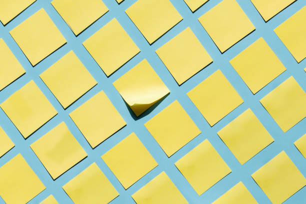 yellow sticky notes on blue background - post it notes стоковые фото и изображения