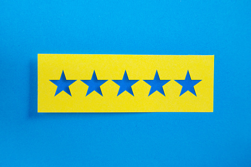 Yellow Sticky Paper With 5 stars Message On Blue Background. Horizontal composition with copy space.