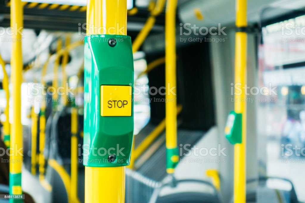 yellow stop button inside a bus stock photo