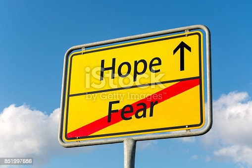 istock Yellow street sign with Hope ahead leaving Fear behind close up 851997686