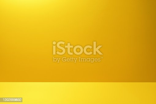 istock Yellow studio background for product placement 1202559832