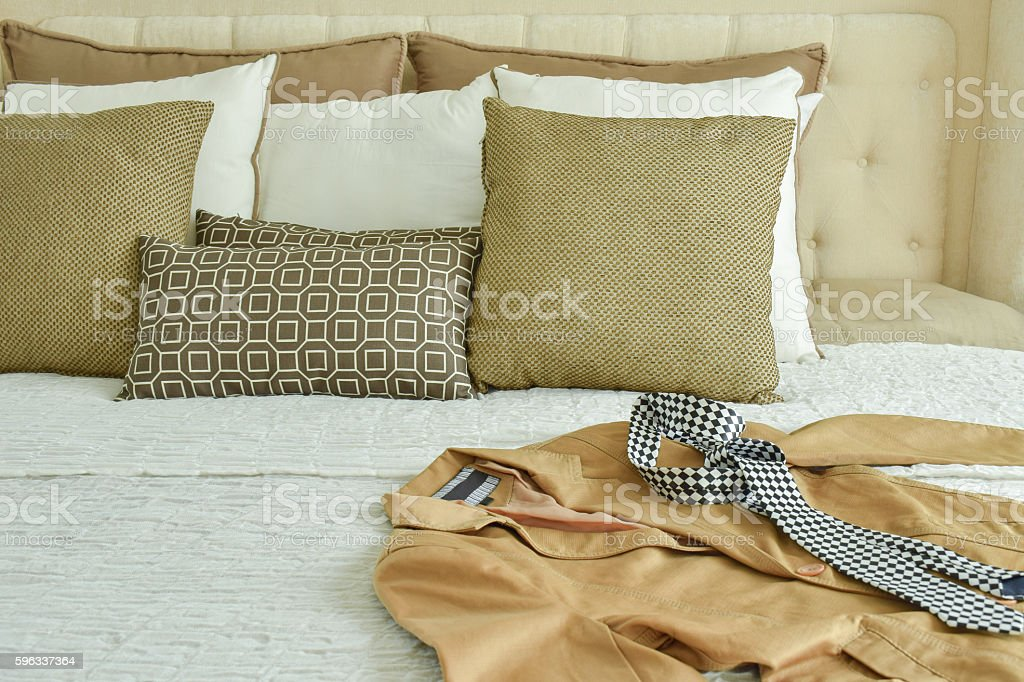 Yellow suit and tie on bed with brown pillows Lizenzfreies stock-foto