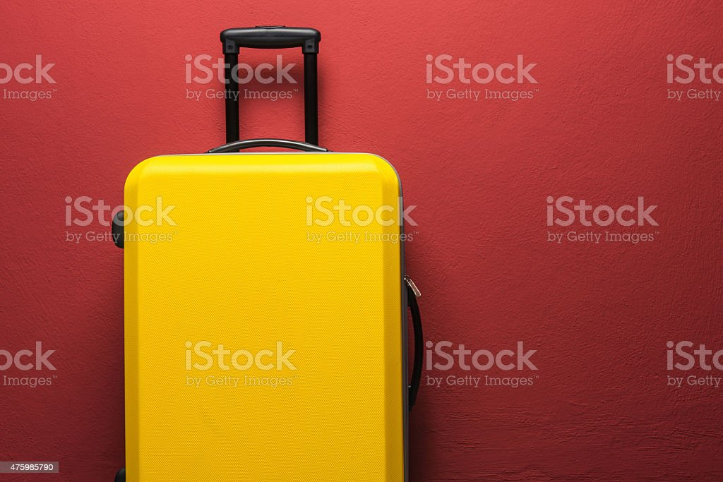 Yellow suitcase with extended handle against red background stock photo