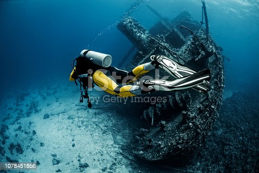 Yellow suited scuba diver exploring a large overgrown shipwreck under the Red Sea.
