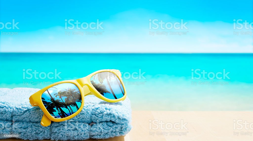 Yellow sunglasses with palm tree on reflection at beach table. stock photo