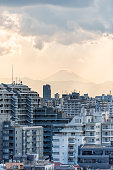 Yellow sunset in Tokyo, Japan Shinjuku cityscape with silhouette view of Mount Fuji and golden sunlight, apartment buildings and mountains during rain