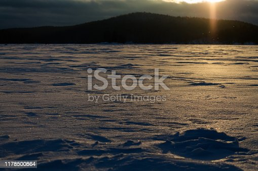 Yellow sunset on the frozen and snow-covered lake. Snow dust. Dense forest in the background
