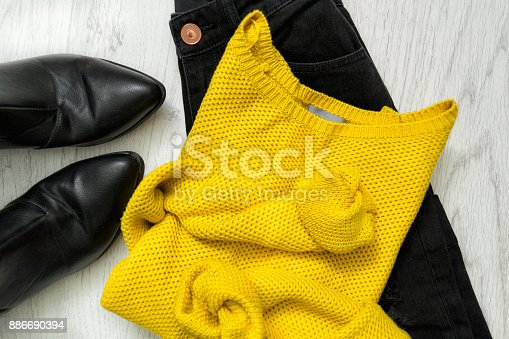 istock Yellow sweater, black jeans and boots. Fashionable concept 886690394