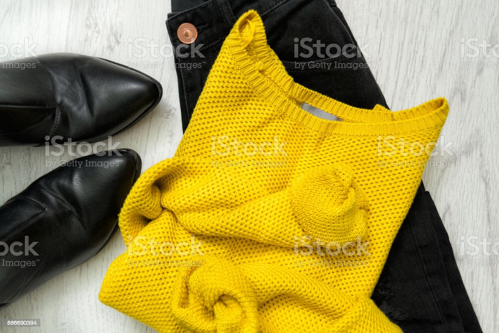 Yellow sweater, black jeans and boots. Fashionable concept stock photo