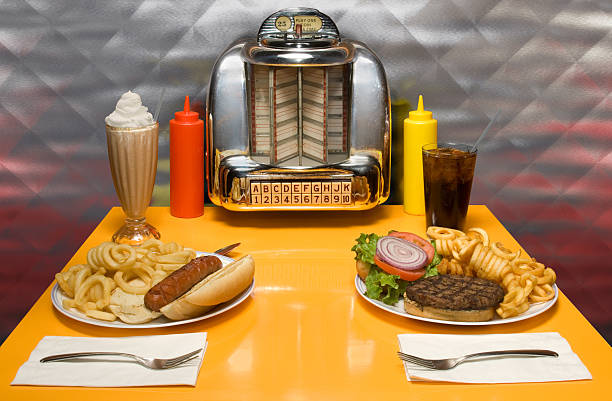 Yellow table with small jukebox and food in a retro diner stock photo