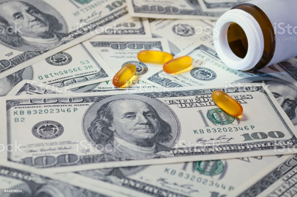 yellow tablet scattered on the bills of 100 dollars stock photo