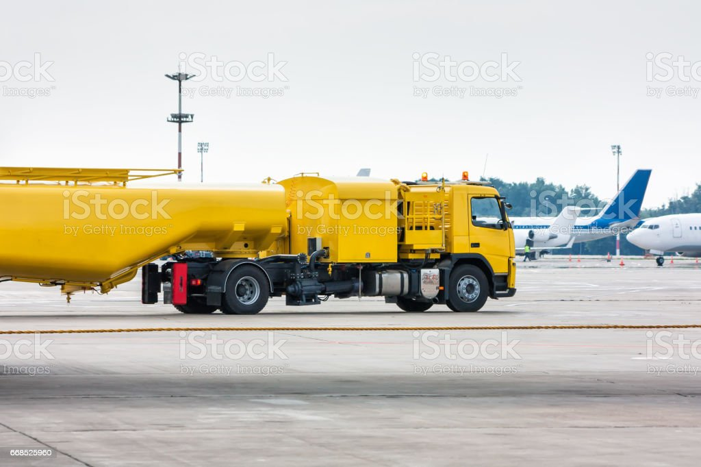 Yellow tank truck aircraft refueler at the airport apron stock photo