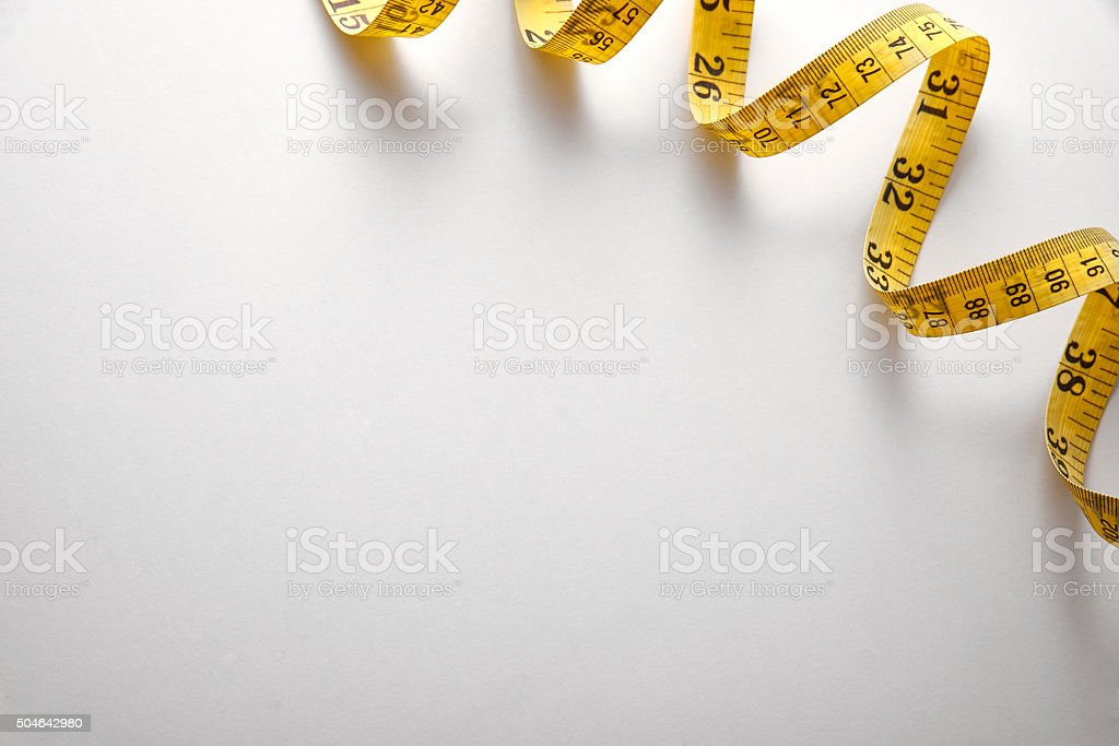 Yellow tape measure in meters and inches background stock photo