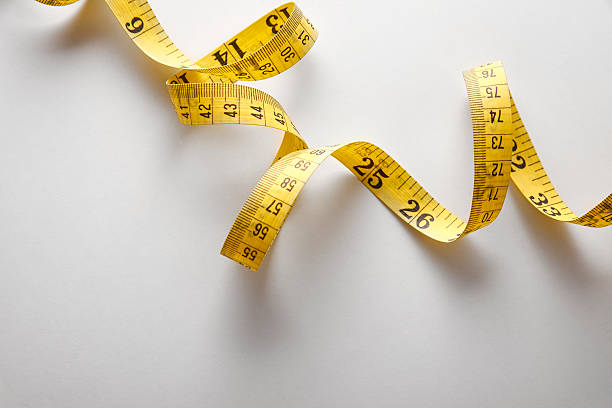 Yellow tape measure in meters and inches in a spiral Yellow tape measure in meters and inches in a spiral on white table. Top view. Horizontal composition. tape measure stock pictures, royalty-free photos & images