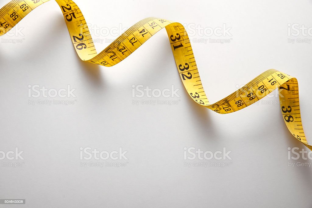 Yellow tape measure in meters and inches spiral and diagonal stock photo