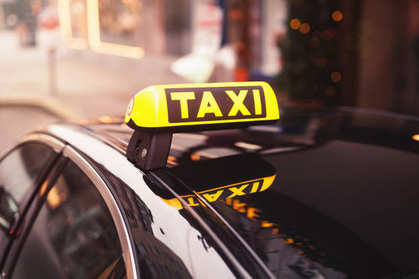 yellow taxi car roof sign at night. taxi car on the street at night stock photo