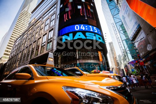 New York City, United States - September 12, 2013: Yellow taxis  under the Nasdaq Sign surrounded by colorful advertisement neon signs and lot of people walking by