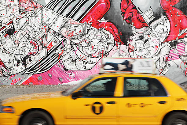 nyc yellow taxi speeds past how nosm street art mural - lower east side manhattan stock pictures, royalty-free photos & images