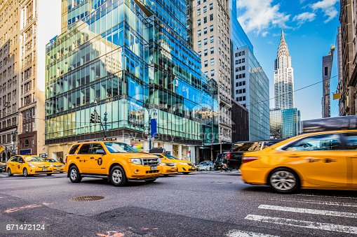 Blurred motion of yellow taxis on busy city street. View of Chrysler Building and modern skyscrapers in New York City. Travel locations.