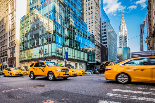 yellow taxis on busy street in new york city - chrysler building stock photos and pictures