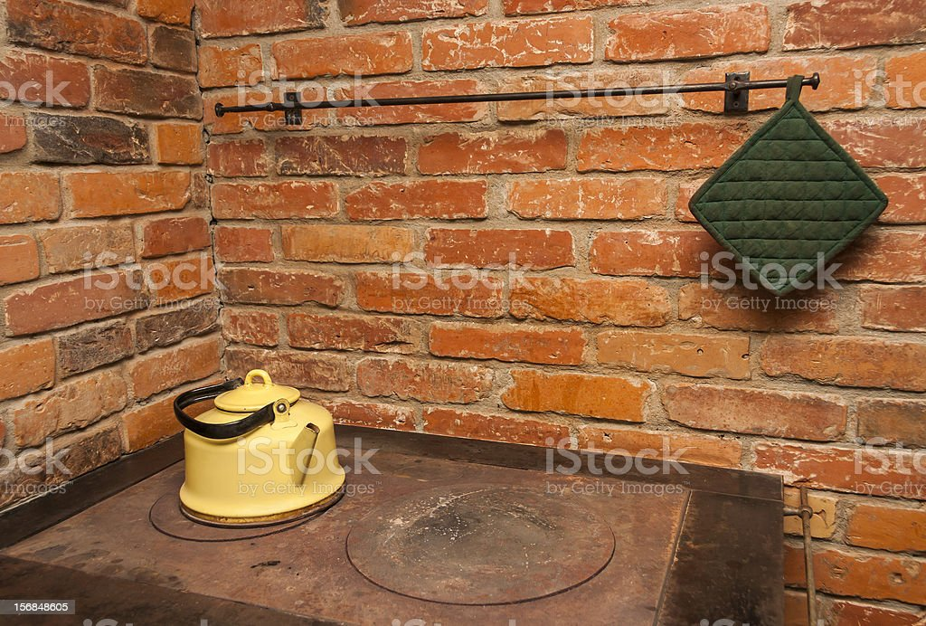 Yellow tea pot on a stove and red brick wall royalty-free stock photo