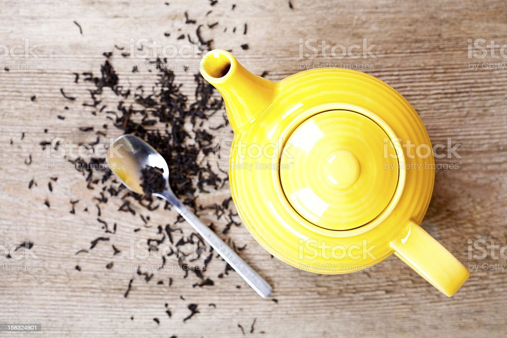 yellow teapot with spoon and tea royalty-free stock photo