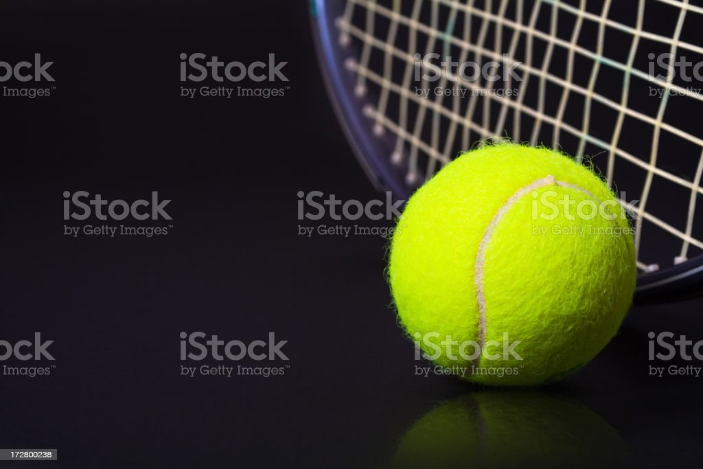 Yellow tennis ball and racket against black background stock photo