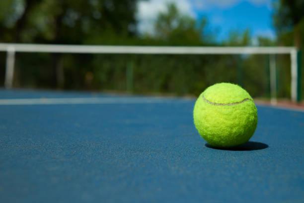 Gelben Tennisball auf blauen Teppich der geöffneten Hof. – Foto