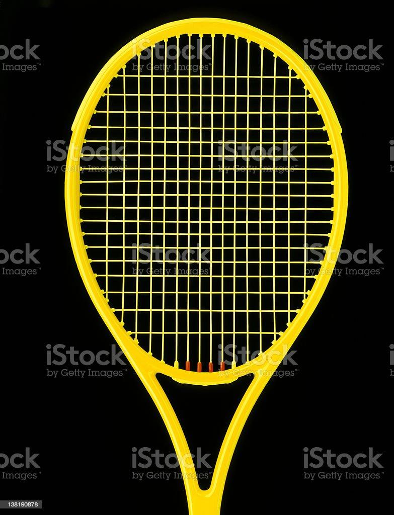 Yellow tennis racket on black background royalty-free stock photo