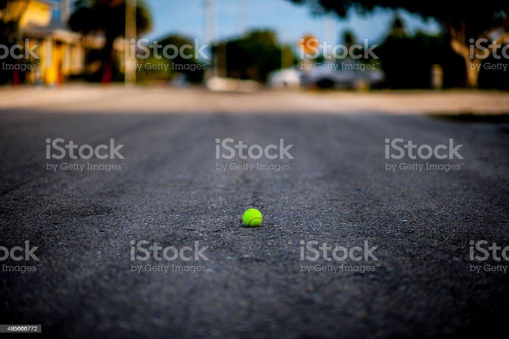 Yellow tennisbal on a tarmac road stock photo