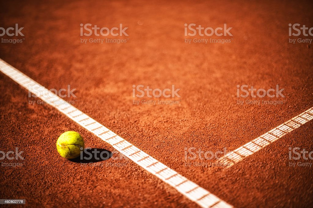 yellow tennisball at the sideline of tennis clay court stock photo
