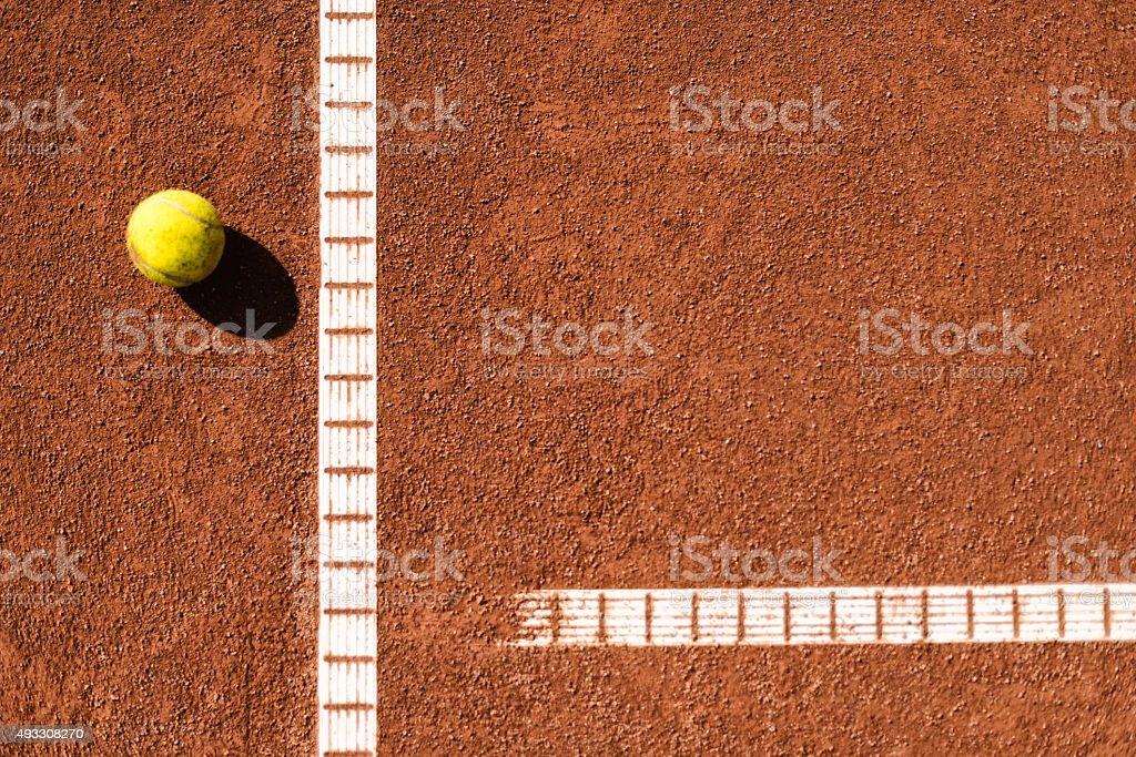 Jaune tennisball aux vestiaires de tennis sur terre battue - Photo