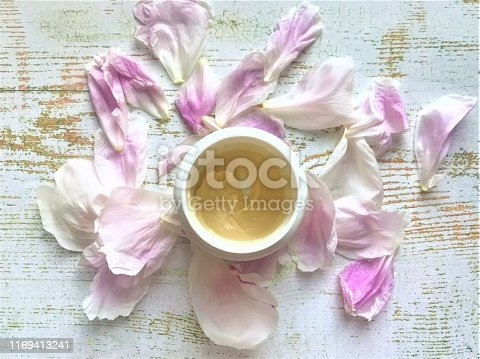 istock Yellow thick fat cream in a white jar for face and body with white-pink peony petals around on a white aged table 1169413241